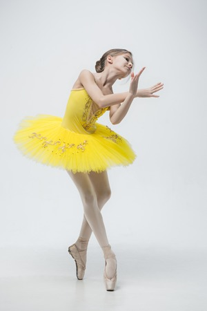 Young classical dancer on white background.