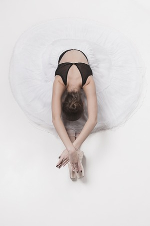Ballerina dancer sitting down with her legs crossed Stock Photo