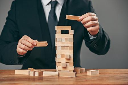 テーブルの上の男と木製の立方体。経営コンセプト
