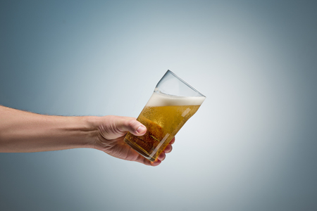 Closeup of a male hand holding up a glass of beer