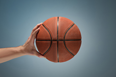 Low key shot of a hand holding a basket ball Archivio Fotografico