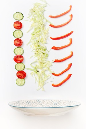 The salad bowl in flight with vegetables: tomato, cucumber, cabbage on white background