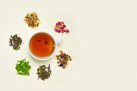 Cup of tea, placer of dry fruit tea and dry flowers on white background, top view