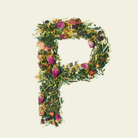 Tea leaf with flowers and fruits, letter P on white background, top view