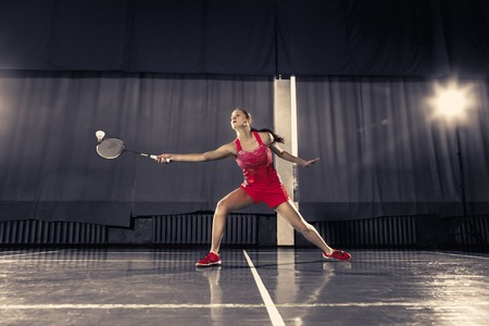 Young woman playing badminton at gym