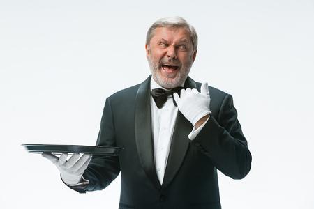 Senior waiter holding tray Фото со стока