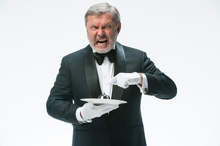 Senior waiter holding bell