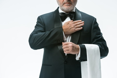 Senior waiter with white towel. Sign language in the restaurant