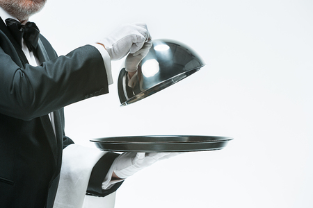 Close up waiter hand with tray and metal cloche lid cover 写真素材