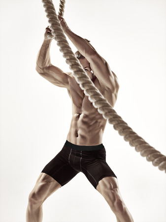 Attractive muscular man working out with heavy ropes. Photo of handsome man in sportswear isolated on white background.