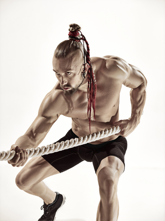 Attractive muscular man working out with heavy ropes.