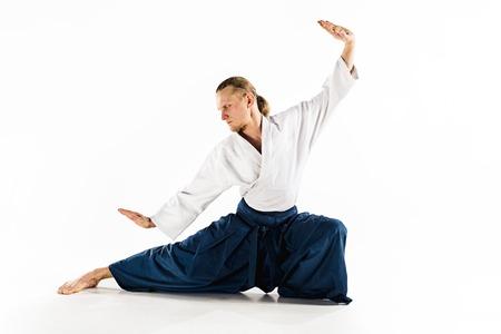 合気道マスターは防衛姿勢を練習します。健康的なライフスタイルとスポーツのコンセプト。白い背景に白い着物のあごひげを持つ男。