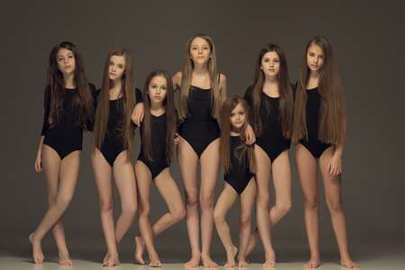 The group of teen girls posing at white studio