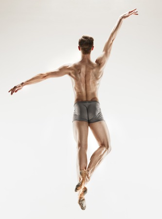 The male athletic ballet dancer performing dance isolated on white background.