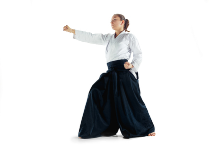 Aikido master practices defense posture. Healthy lifestyle and sports concept. Woman in white kimono on white background. 스톡 콘텐츠