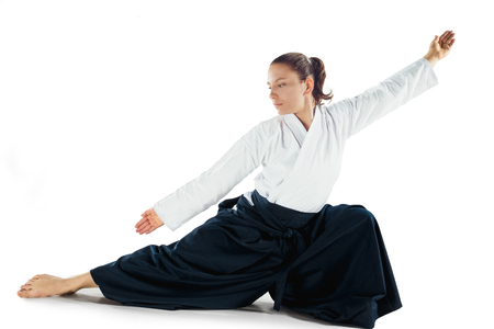 Aikido master practices defense posture. Healthy lifestyle and sports concept. Woman in white kimono on white background. Stok Fotoğraf