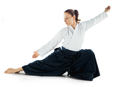 Aikido master practices defense posture. Healthy lifestyle and sports concept. Woman in white kimono on white background. Stock Photo