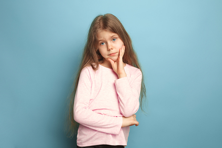 The thoughtful girl. Teen girl on a blue background. Facial expressions and people emotions concept