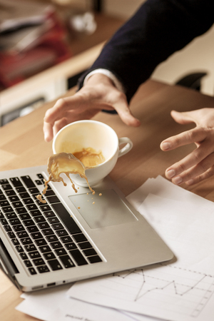 Coffee in white cup spilling on the table in the morning working day at office table Banque d'images