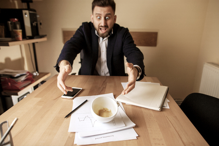 Coffee in white cup spilling on the table in the morning working day at office table Stock Photo