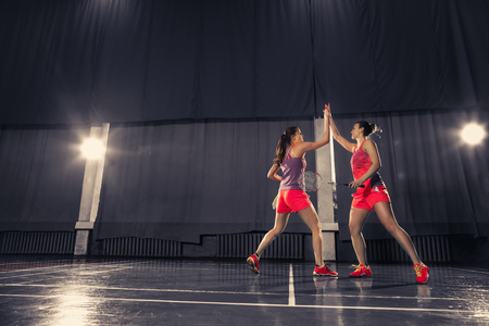Young women playing badminton at gym Stock Photo