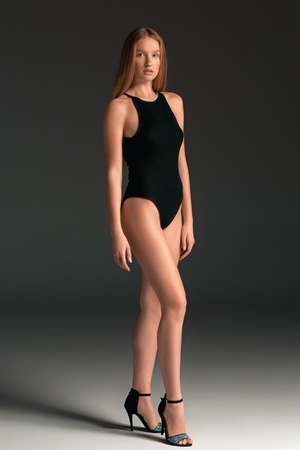 Fashion woman portrait. Beautiful young model in a black swimsuit. Studio shot, gray background.