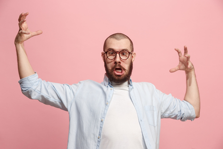 Portrait of an angry man looking at camera isolated on a pink background