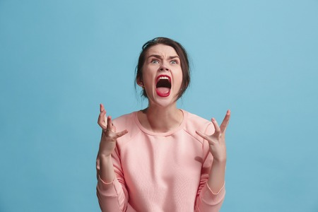 The young emotional angry woman screaming on blue studio background