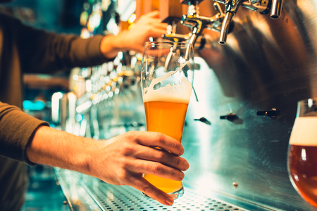 Hand of bartender pouring a large lager beer in tap. Banco de Imagens - 95955677