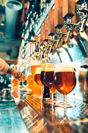 Mano del barman vertiendo una gran cerveza en el grifo.
