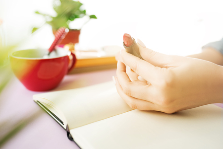 The female hands holding pomade. The trendy pink desk. Stock Photo