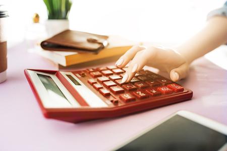 女性は財布、手にクレジットカードを保持し、コストを計算しています