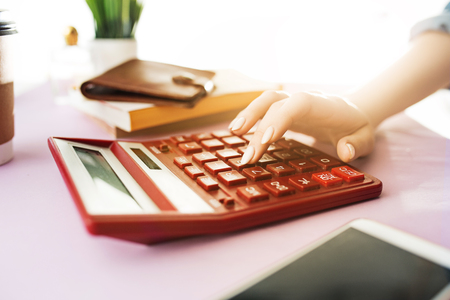 woman is holding purse, credit card in hands and calculating the costs