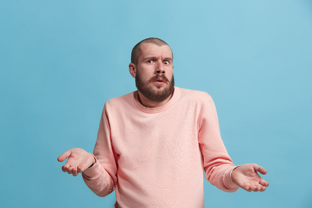 Beautiful man looking suprised and bewildered isolated on blue Stock Photo