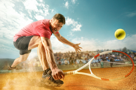 The one jumping player, caucasian fit man, playing tennis on the earthen court with spectators Stockfoto