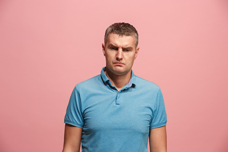 Suspiciont. Doubtful pensive man with thoughtful expression making choice against pink background