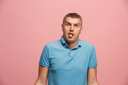 The squint eyed man with weird expression isolated on pink Stock Photo