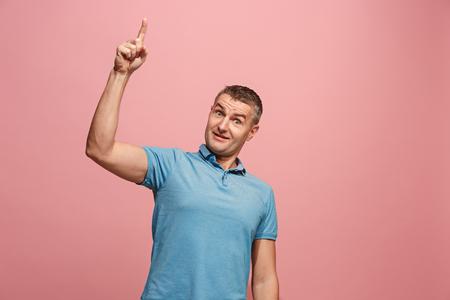 The young attractive man looking suprised isolated on pink