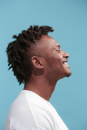 The happy business Afro-American man standing and smiling against blue background. Profile view. Stock Photo