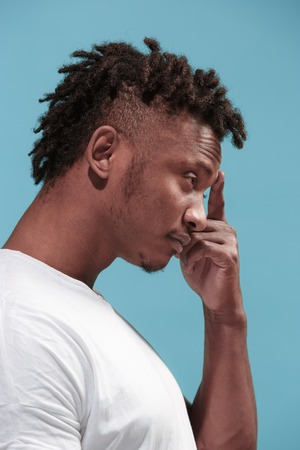 Let me think. Doubtful pensive Afro-American man with thoughtful expression making choice against blue background