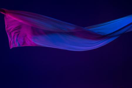 Smooth elegant transparent blue cloth separated on blue background.