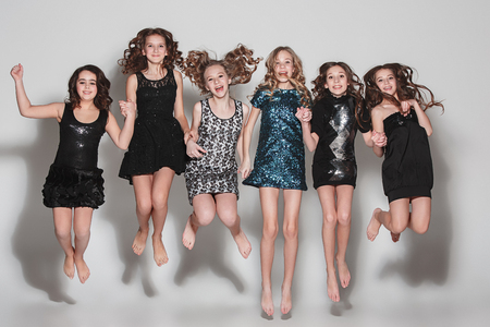 The fashion girls jumping together and looking at camera over gray studio background