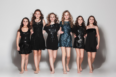 The fashion girls standing together and looking at camera over gray studio background
