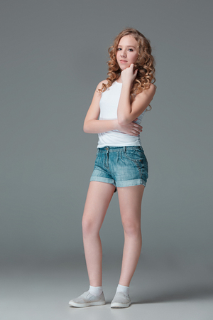 Full length of young slim female girl in denim shorts on gray background