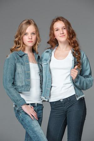 Full length of young slim female girl in denim jeans on gray background