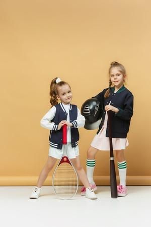 Portrait of two girls as tennis players holding tennis racket. Studio shot. Zdjęcie Seryjne