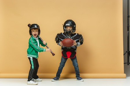 Two happy children show different sport. Studio fashion concept. Emotions concept. Stock Photo