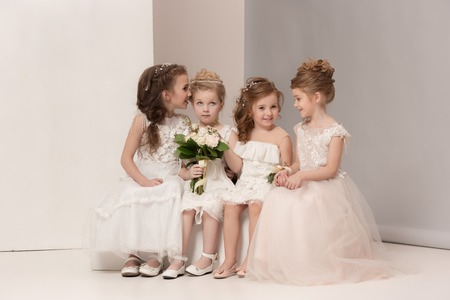 Little pretty girls with flowers dressed in wedding dresses 스톡 콘텐츠