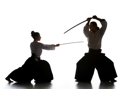 Man and woman fighting and training aikido on white studio background