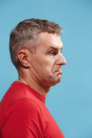 Suspiciont. Doubtful pensive man with thoughtful expression making choice against blue background